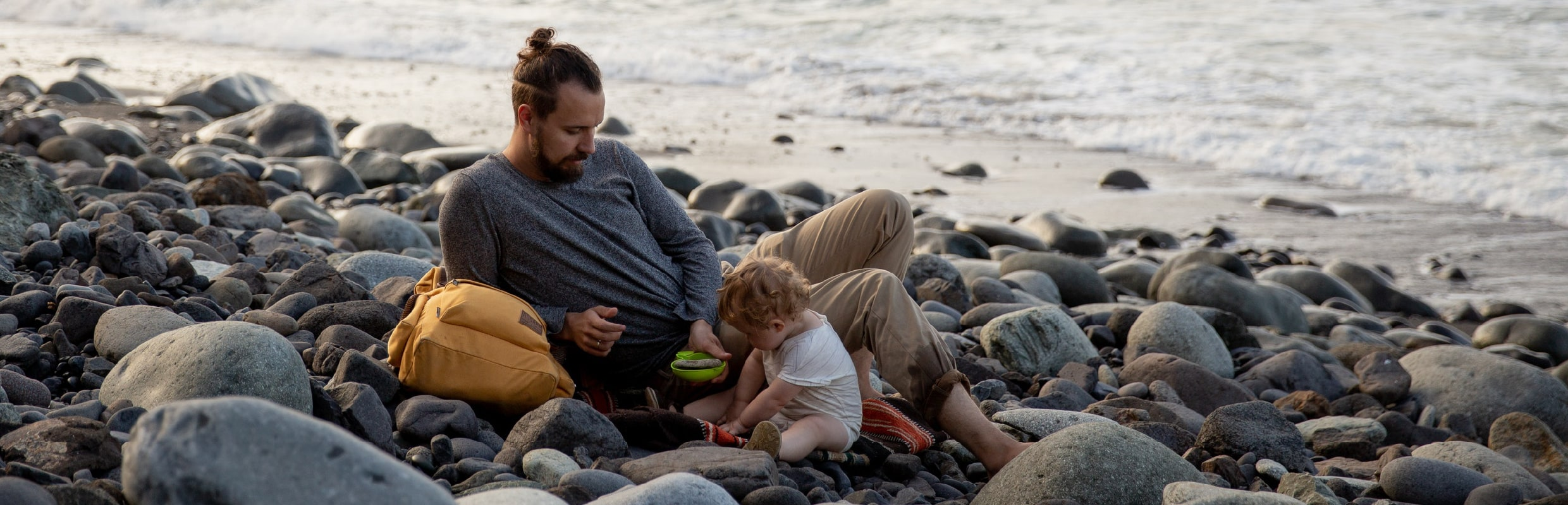 Dad and child on stony beach playing