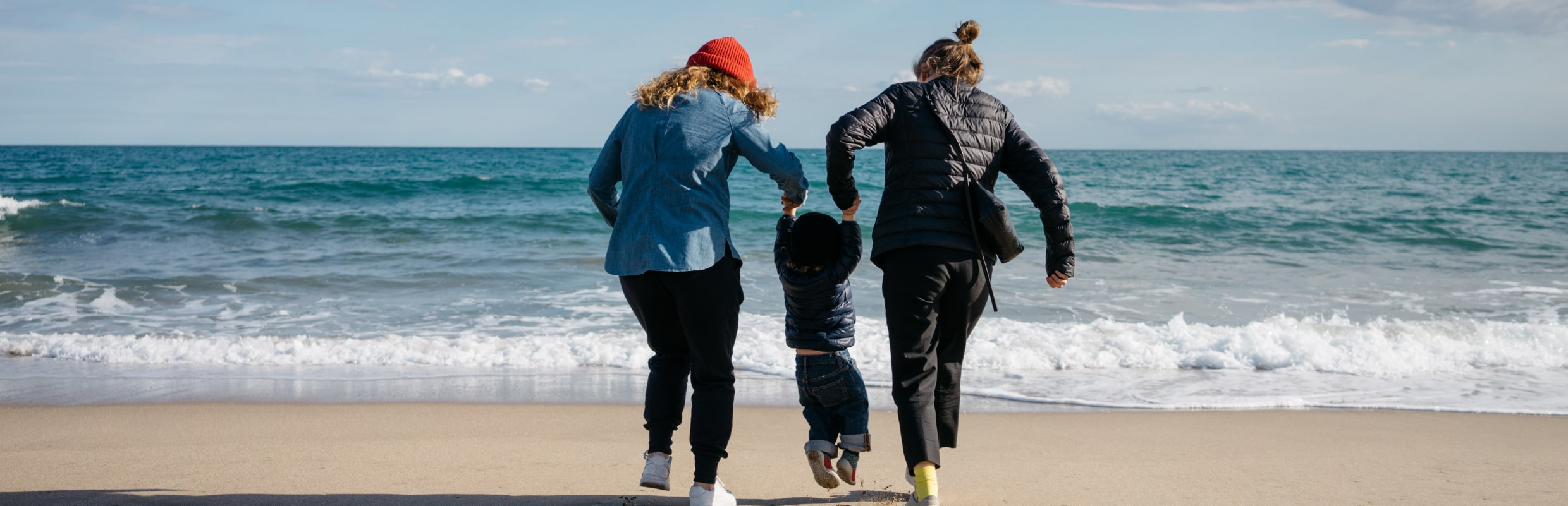 Gay couple with a child at the beach