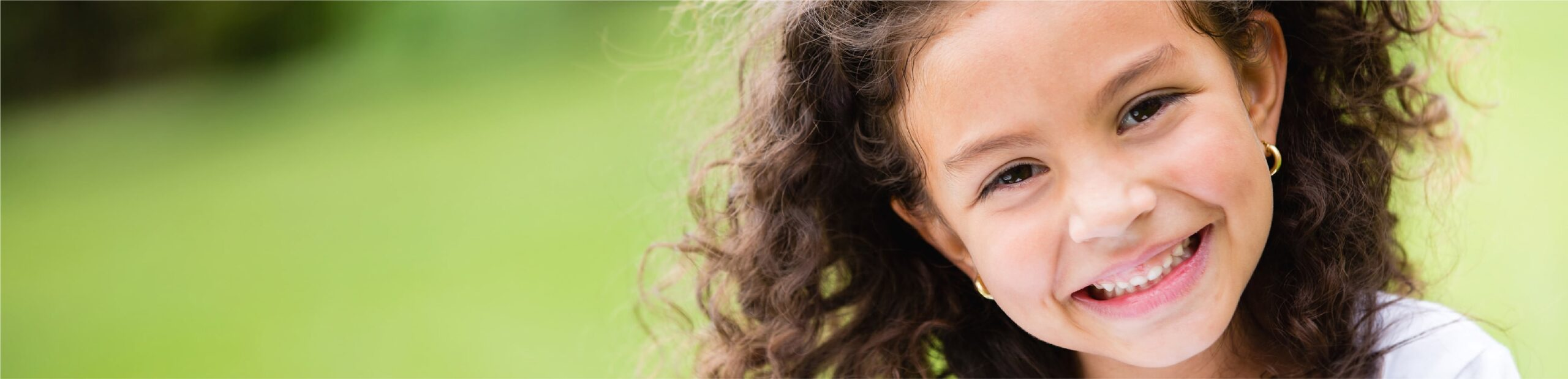 young female with curly brown hair smiling