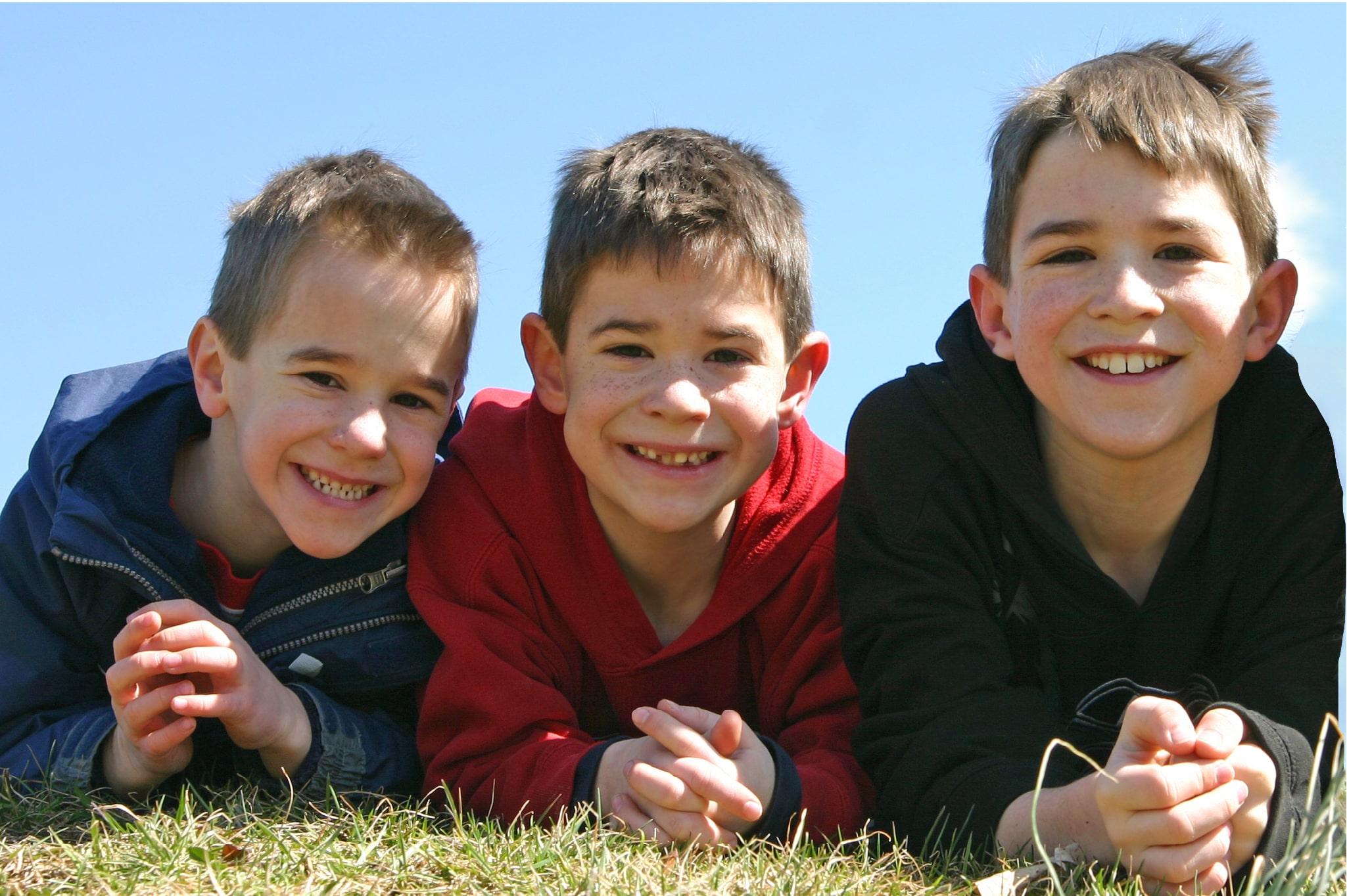 Three boys smiling lying on the grass