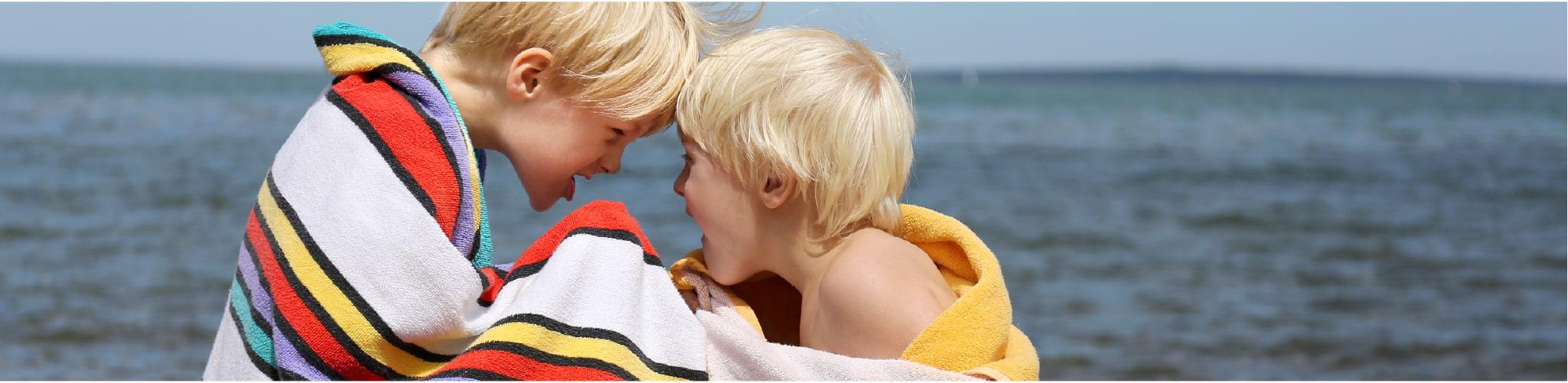 Two blonde boys playing in beach towels near the sea