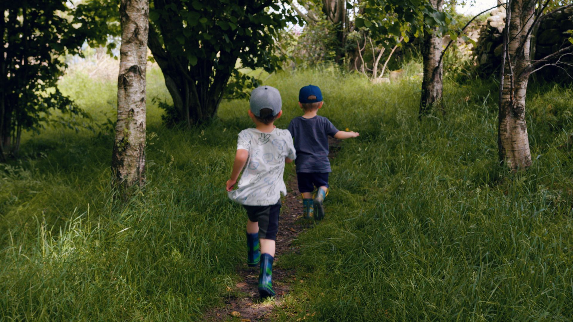 Two young boys running through a field