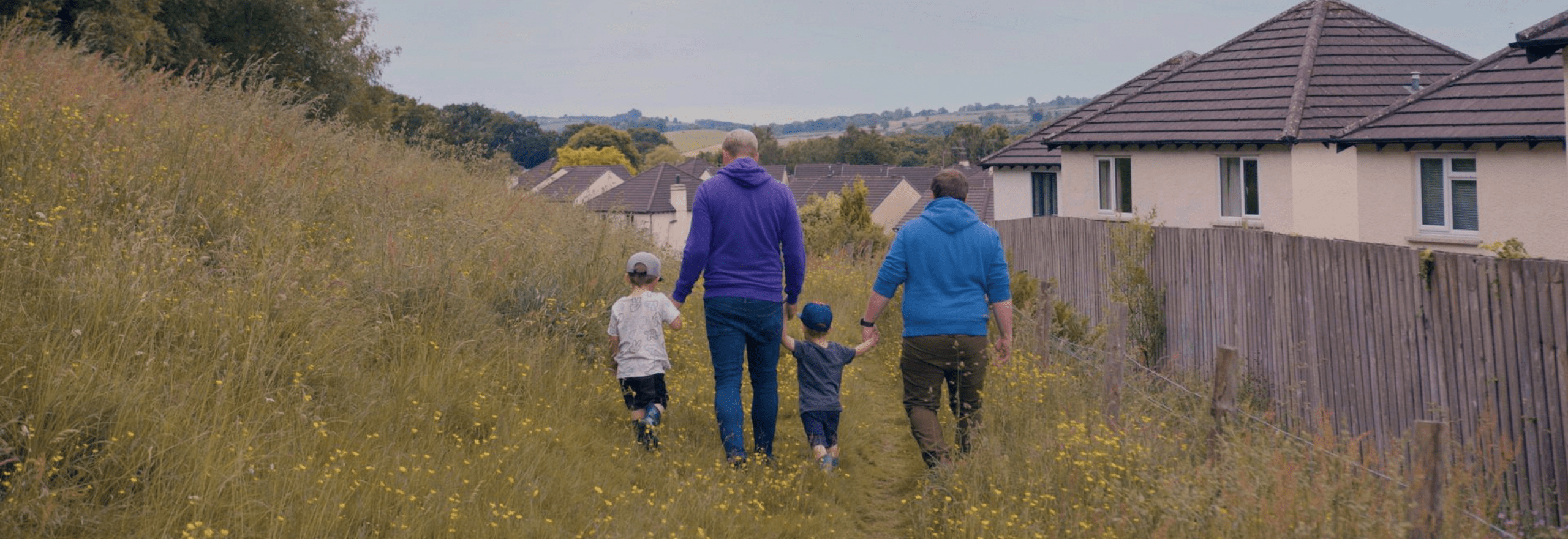 Banner featuring two dads and two boys walking